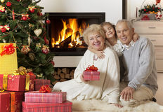 Senior couple with granddaughter enjoying Christmas Royalty Free Stock Image