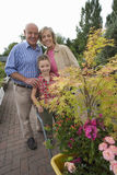 Senior couple and granddaughter (8-10) in garden centre, portrait Royalty Free Stock Photo