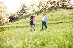 Senior couple with granddaughter outside in spring nature. royalty free stock image