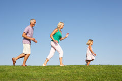 Senior couple, with granddaughter,running. Senior couple, with granddaughter,  running though field in the sun Royalty Free Stock Image