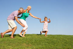 Senior couple, with granddaughter,running. Senior couple, with granddaughter, running though field in the sun stock images
