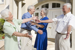 Senior couple greeting friends. Outside house Stock Photo