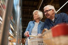 Senior Couple Grocery Sopping. Low angle portrait of modern senior couple grocery shopping in supermarket, smiling happily while choosing frozen foods standing stock photos