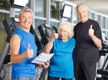 Senior couple in gym holding thumbs up Stock Photos