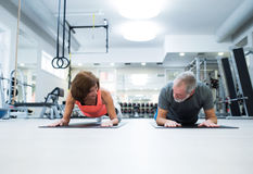 Senior couple in gym in plank position working abs Stock Photo