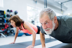 Senior couple in gym working out, doing push ups Stock Photography