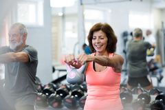 Senior couple in gym working out using kettlebells. stock photos