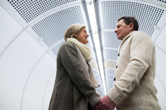Senior couple in hallway of subway holding hands Stock Image