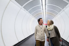 Senior couple in hallway of subway pulling trolley luggage. Stock Photos