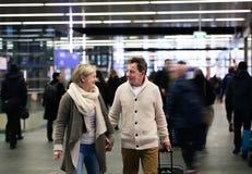 Senior couple in hallway of subway pulling trolley luggage. Stock Photo