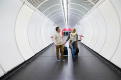 Senior couple in hallway of subway pulling trolley luggage. Royalty Free Stock Photo