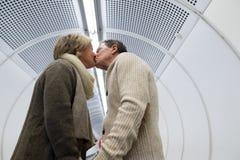 Senior couple in hallway of subway pulling trolley luggage. Royalty Free Stock Photos