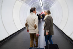 Senior couple in hallway of subway pulling trolley luggage. Stock Photography