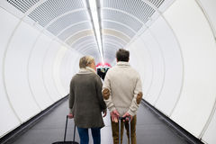 Senior couple in hallway of subway pulling trolley luggage. Royalty Free Stock Photography