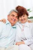 Senior couple happy smile embrace sitting sofa Stock Photography