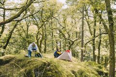 Senior Couple Wild Camping Together. Senior couple have chosen their spot in the woodlands to set up for wild camping. The women is setting up the tent and the Stock Photo