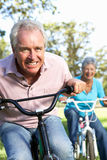 Senior couple haveing fun on childrens bike Royalty Free Stock Image