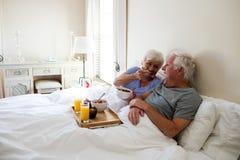 Senior couple having breakfast in the bedroom Stock Photography