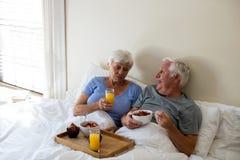 Senior couple having breakfast in the bedroom Stock Images