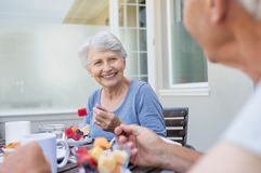 Senior couple having breakfast. Happy senior women eating fresh fruits during breakfast. Cheerful old lady with grey hair enjoying healthy breakfast with her stock photography