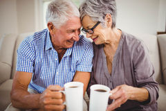 Senior couple having coffee in living room Stock Photography