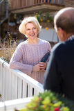 Senior couple having conversation. Beautiful smiling retired women with gardening tools in her hands talking to a senior men on a terrace stock photos