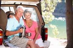 Senior couple having country picnic. In boot of car smiling at camera Stock Photo