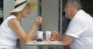 Senior couple having desserts and coffee in cafe stock video