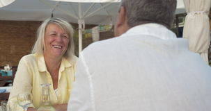 Senior couple having excited talk in summer cafe stock footage
