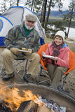 Senior Couple Having Food At Campfire Stock Images