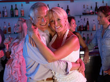 Senior Couple Having Fun In Busy Bar. Senior Couple Having Fun Hugging In Busy Bar stock photography