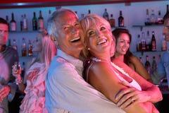 Senior Couple Having Fun In Busy Bar. Senior Couple Having Fun Laughing In Busy Bar stock photography