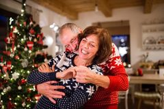 Senior couple having fun at Christmas time. Beautiful senior couple in woolen sweaters with nordinc pattern at Christmas time, hugging. Man and women having fun Stock Images