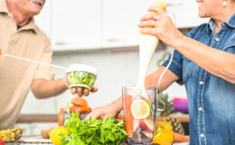 Senior Couple Having Fun In Kitchen With Healthy Veggie Food Stock Photography