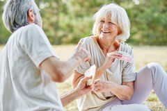 Senior couple having fun and playing a card game. In summer in the nature stock photo