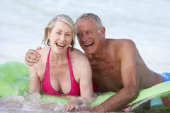 Senior Couple Having Fun In Sea On Airbed Stock Images