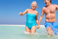Senior Couple Having Fun In Sea On Beach Holiday Stock Photo