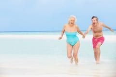 Senior Couple Having Fun In Sea On Beach Holiday Royalty Free Stock Photos