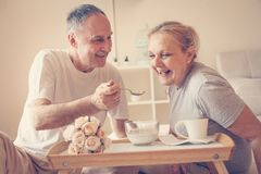 Senior couple having healthy breakfast together in bed. Close up Royalty Free Stock Photos