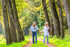 Senior couple having leisure walk in woods Stock Images