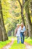 Senior couple having leisure walk in woods Stock Images