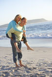 Senior Couple Having Piggy Bck On Sandy Beach Stock Images