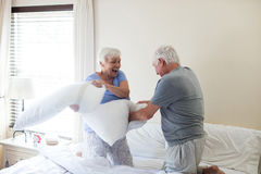 Senior couple having pillow fight on bed. In bedroom stock photos