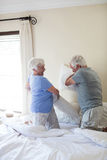 Senior couple having pillow fight on bed. In bedroom royalty free stock image