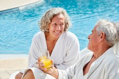 Senior couple having a refreshment by the pool. Senior couple relaxes by the pool with a refreshing spa vacation stock photo