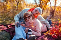 Senior couple having tea in autumn forest. Happy man and woman enjoying picnic and nature. Senior couple having tea in autumn forest. Happy men and women royalty free stock images