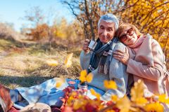 Senior couple having tea in autumn forest. Happy man and woman enjoying picnic and nature. Senior couple having tea in autumn forest. Happy men and women royalty free stock photography
