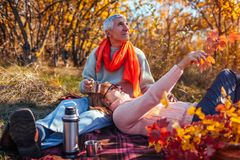 Senior couple having tea in autumn forest. Happy man and woman enjoying picnic and nature. Senior couple having tea in autumn forest. Happy men and women royalty free stock photo