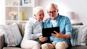 Senior couple having video call on tablet computer. Family, online communication, age and people concept - happy senior couple with tablet computer having video stock footage