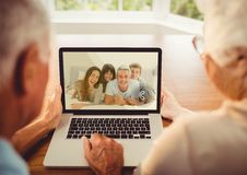 Senior couple having a video call with their family on laptop. Rear view of senior couple having a video call with their family on laptop Stock Photos